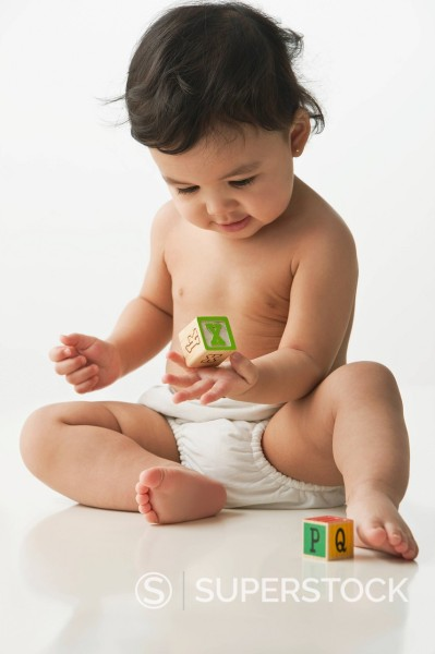 Mixed race baby girl playing with alphabet blocks : Stock Photo