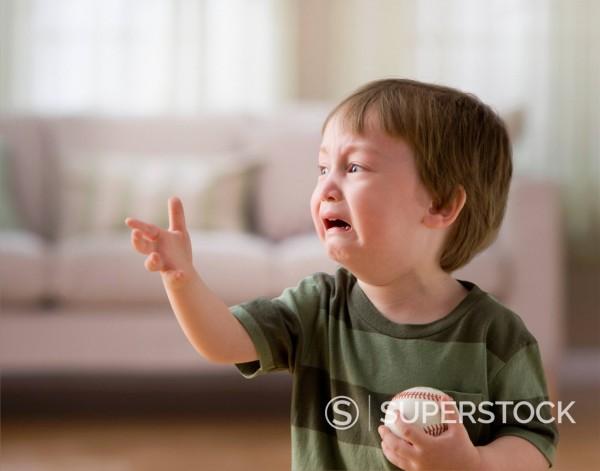 Mixed race boy crying and holding baseball : Stock Photo
