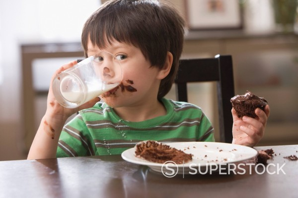 Mixed race boy eating cupcake and drinking milk : Stock Photo