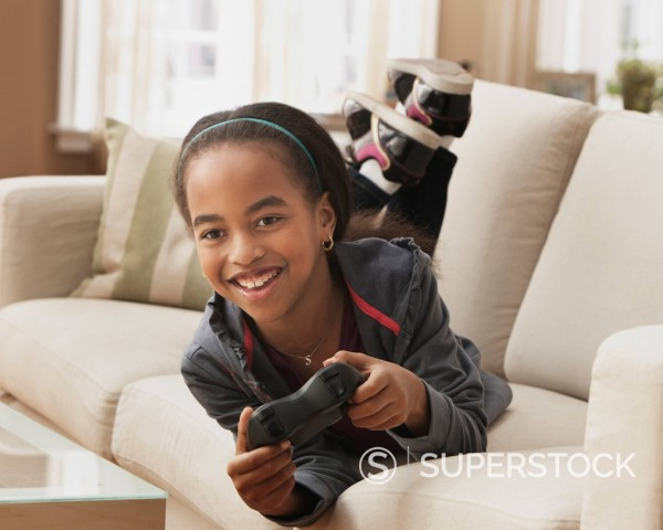 Stock Photo: 1589R-153264 African American girl playing video game