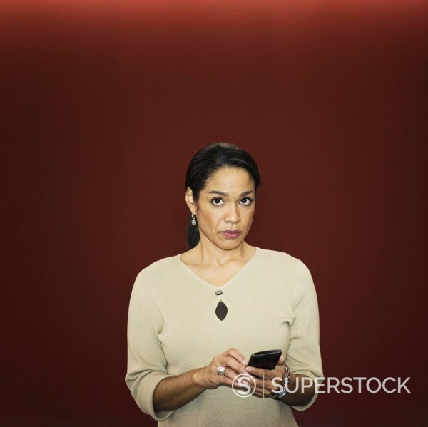 Stock Photo: 1589R-153480 Black businesswoman text messaging on cell phone