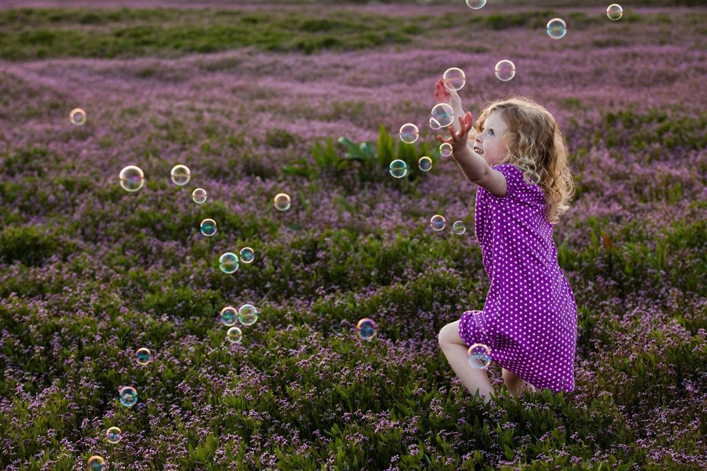 Stock Photo: 1589R-153598 Caucasian girls chasing bubbles in field of flowers
