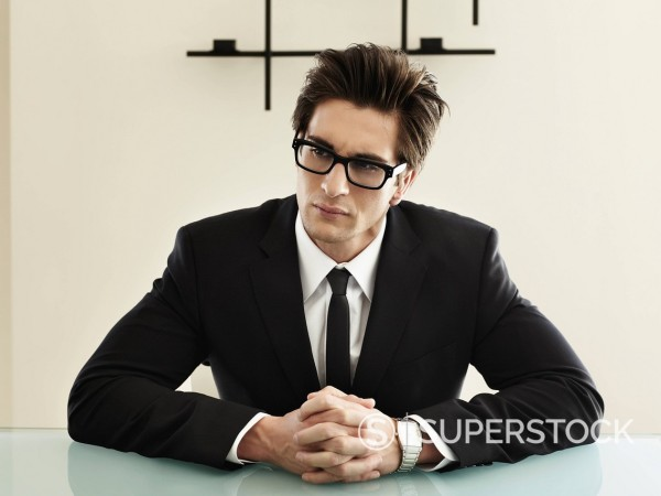 Trendy Caucasian businessman sitting at desk : Stock Photo