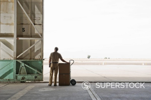 Stock Photo: 1589R-153867 Caucasian worker with boxes in empty warehouse