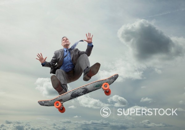 Mixed race businessman on skateboard in sky : Stock Photo