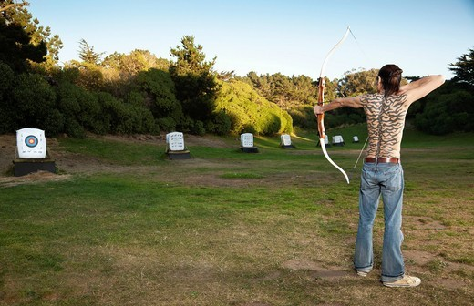 Mixed race archer aiming bow and arrow at target : Stock Photo