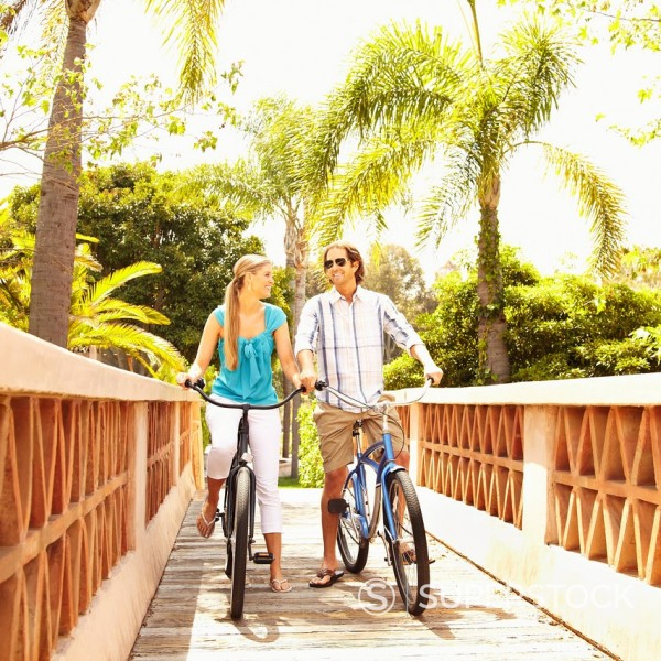 Stock Photo: 1589R-154030 Caucasian couple riding bikes over bridge
