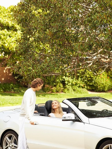 Caucasian man helping wife into convertible : Stock Photo