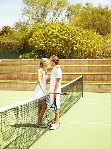 Caucasian couple playing tennis and hugging : Stock Photo