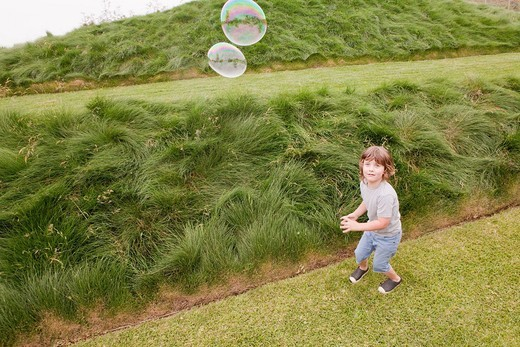 Caucasian boy looking at floating bubbles : Stock Photo