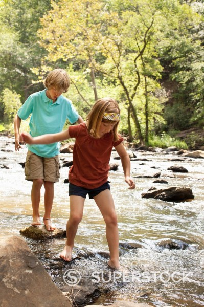 Stock Photo: 1589R-154209 Caucasian brother and sister standing on rocks in stream