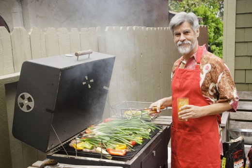 Middle-aged man grilling vegetables : Stock Photo