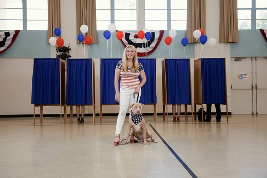 Woman and dog standing in polling place : Stock Photo