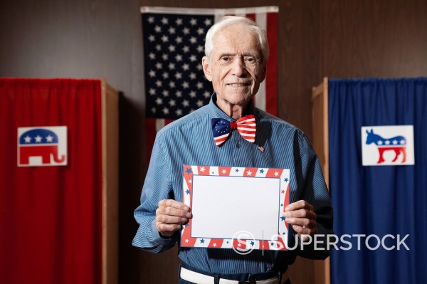 Stock Photo: 1589R-155422 Caucasian voter holding blank card in polling place