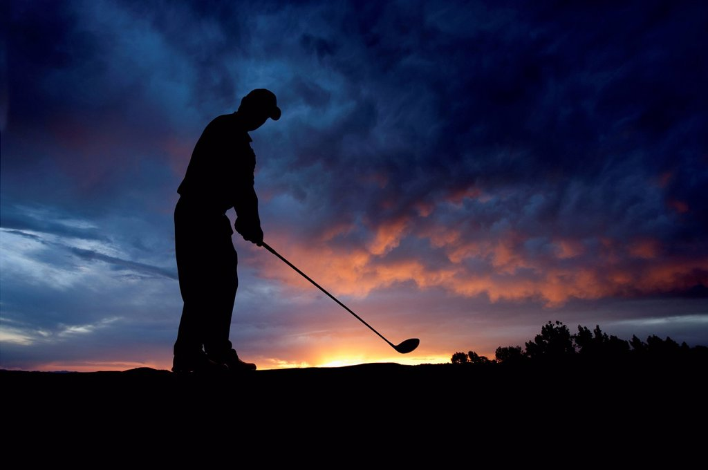 Stock Photo: 1589R-155533 Caucasian golfer swinging golf club at sunset