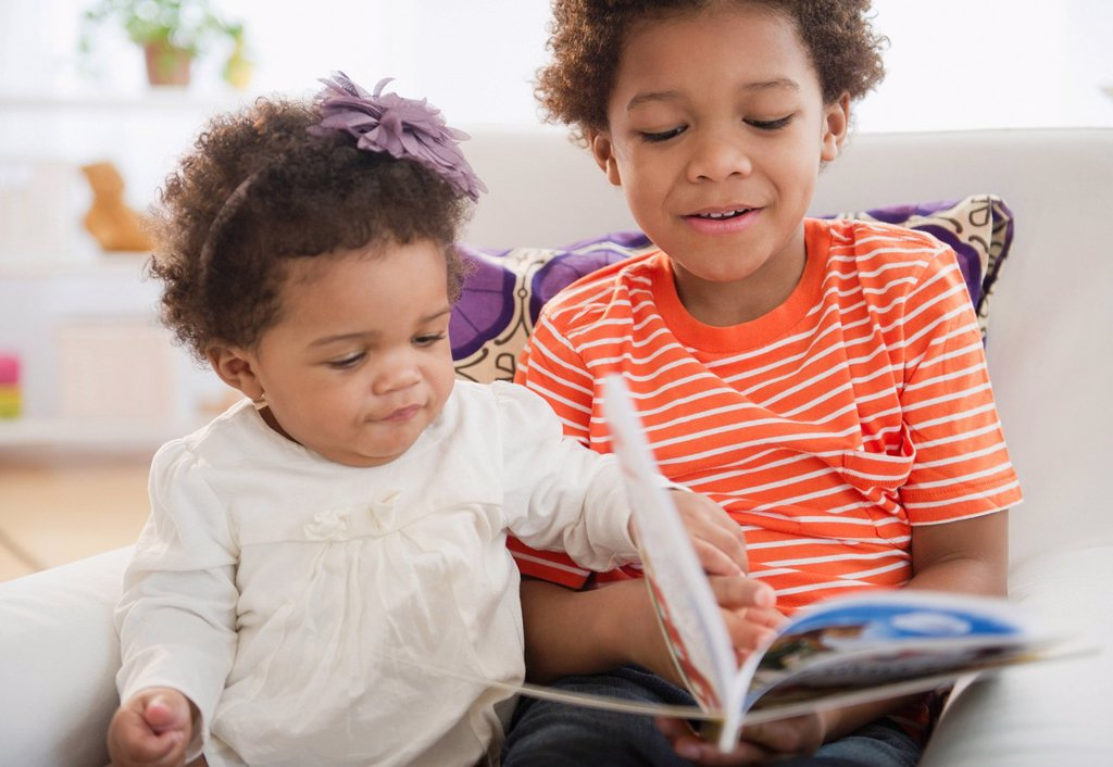 Stock Photo: 1589R-155872 Black brother reading book to sister