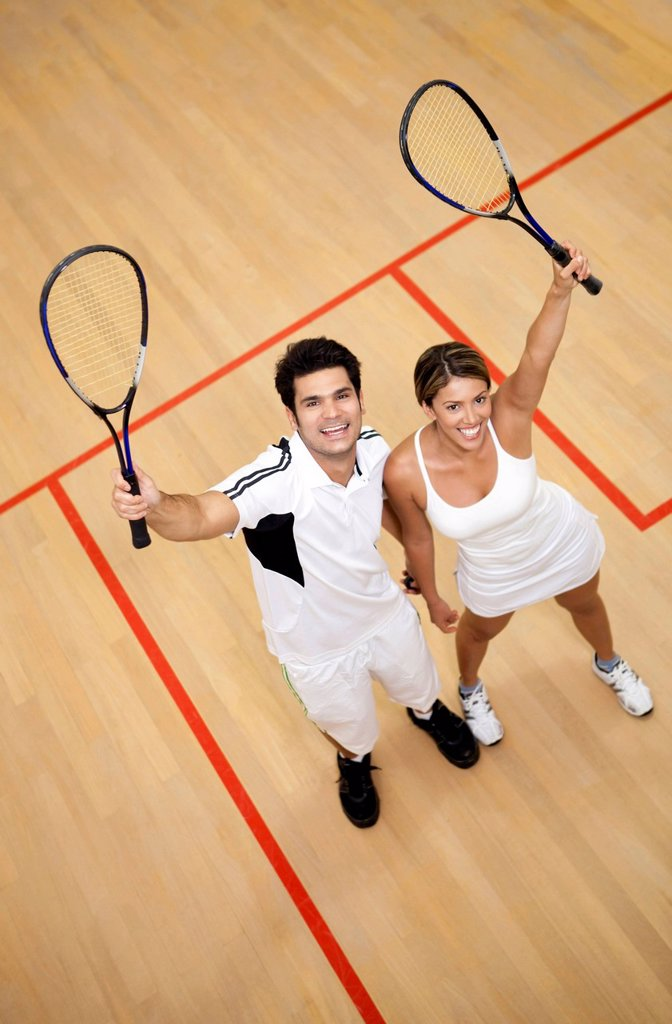 Hispanic couple raising squash racquets : Stock Photo