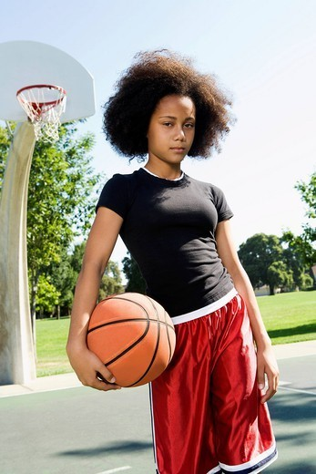 Serious teenage girl holding basketball on court : Stock Photo