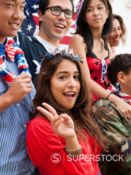 Friends holding American flags on Fourth of July : Stock Photo