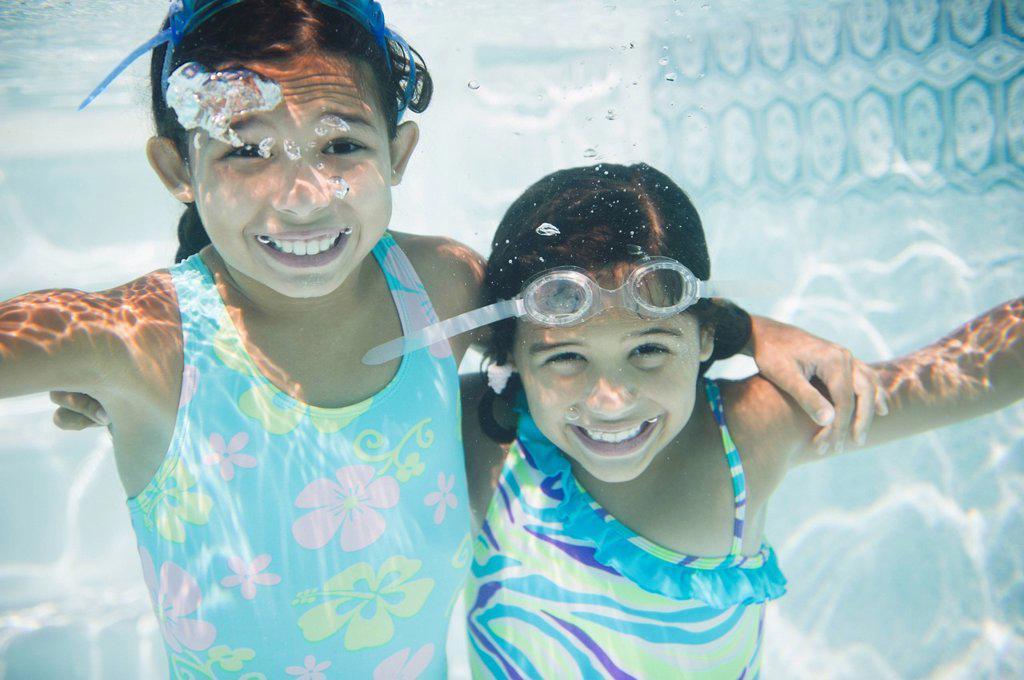 Stock Photo: 1589R-156366 Hispanic girls swimming under water