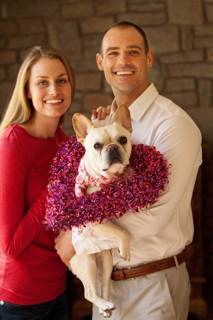 Caucasian couple holding dog : Stock Photo