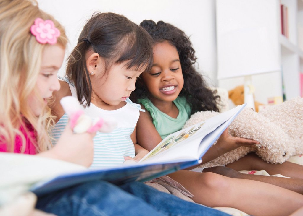 Girls reading book together : Stock Photo