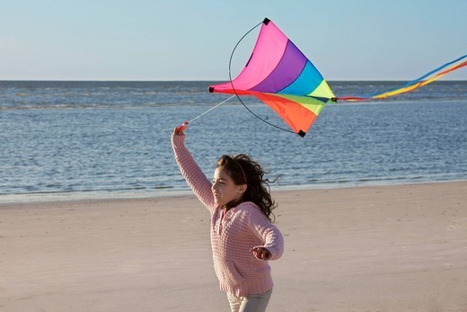 Mixed race girl flying kite on beach : Stock Photo