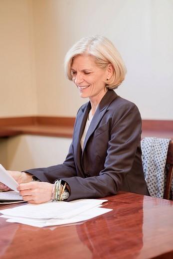 Caucasian businesswoman reading report : Stock Photo