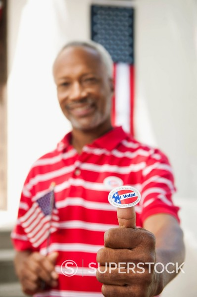 Stock Photo: 1589R-156749 African American man holding an I Voted sticker