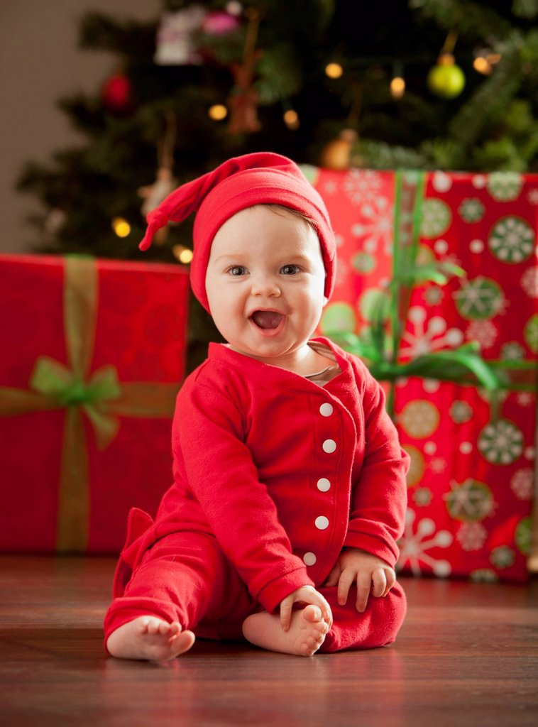 Caucasian baby boy sitting near Christmas tree : Stock Photo
