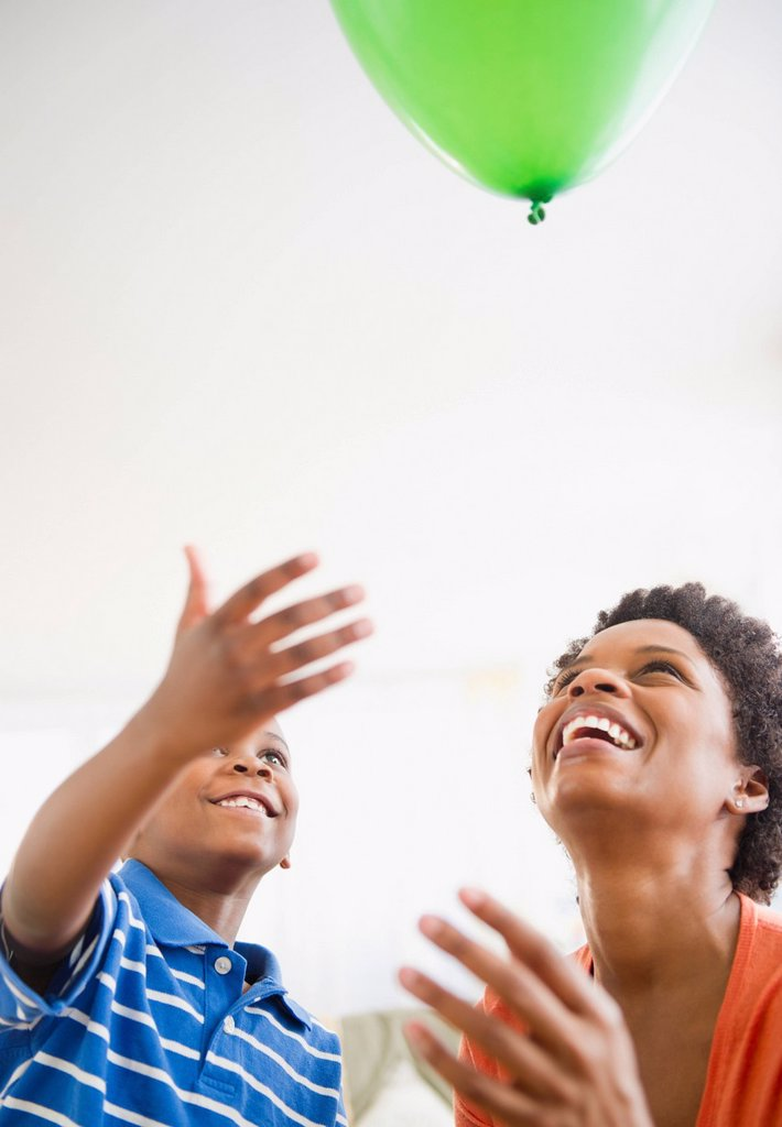 Black mother and son watching floating balloon : Stock Photo