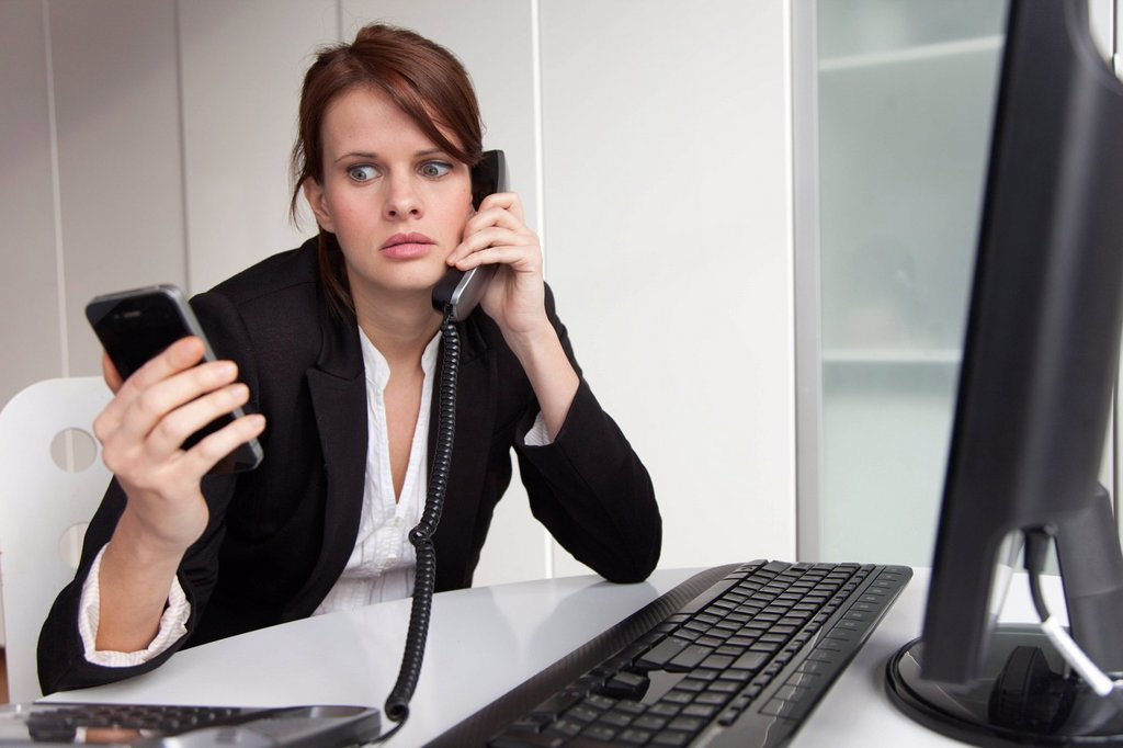 Stock Photo: 1589R-156898 Businesswoman holding cell phone and talking on landline phone