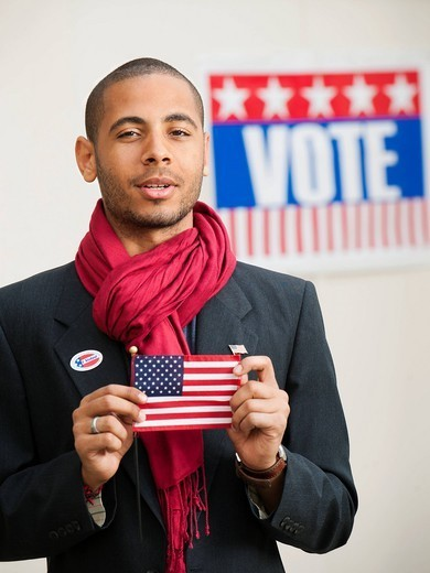 Hispanic man holding American flag with Vote sign in background : Stock Photo