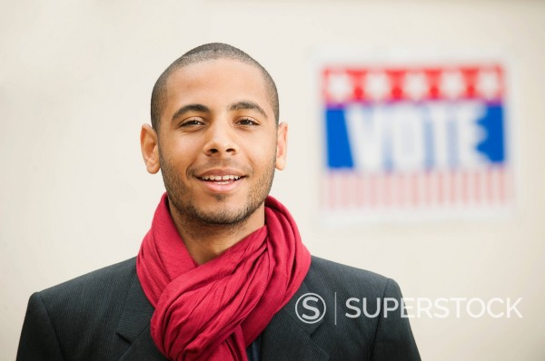 Stock Photo: 1589R-157108 Smiling Hispanic man with Vote sign in background