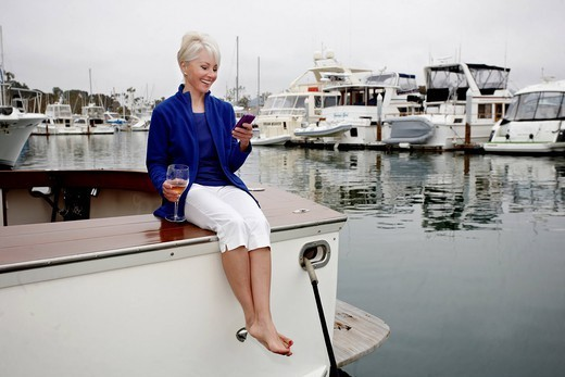 Woman sitting on boat text messaging on cell phone : Stock Photo