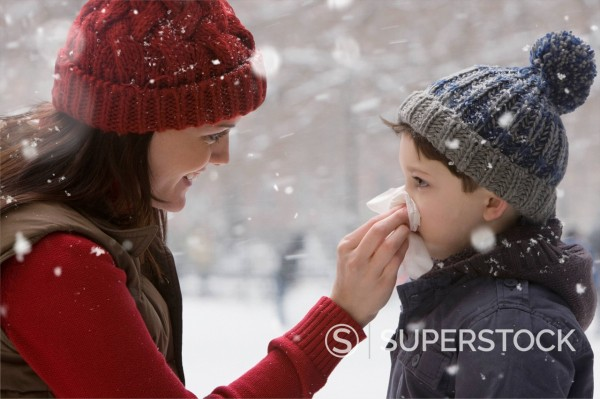 Caucasian mother wiping son´s nose in the snow : Stock Photo