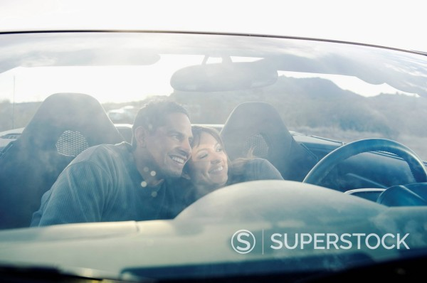 Hispanic couple unwinding in sports car : Stock Photo
