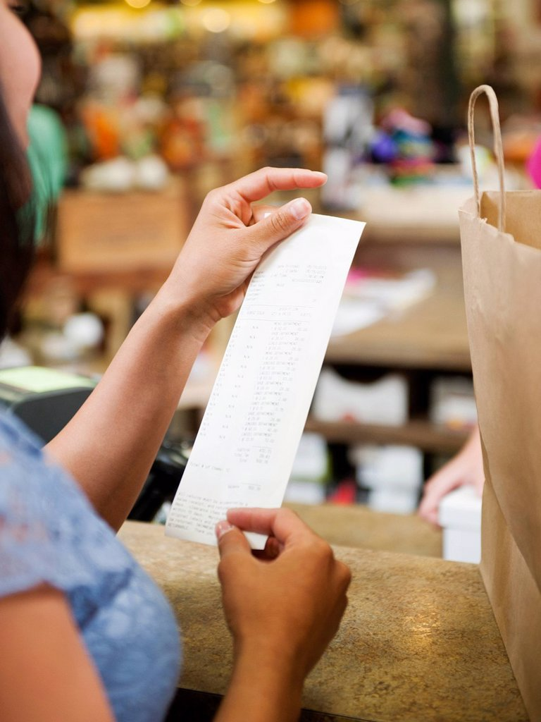 Stock Photo: 1589R-157550 Mixed race woman looking at shopping receipt