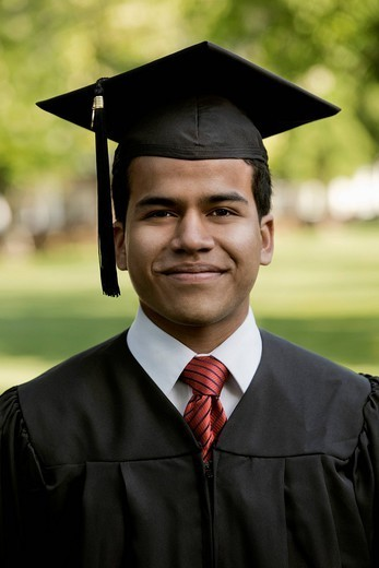Hispanic college graduate in cap and gown : Stock Photo