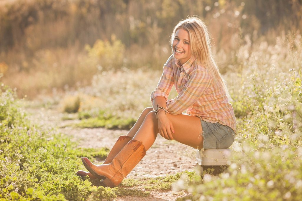 Caucasian woman sitting on tackle box in field : Stock Photo