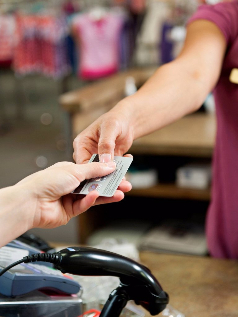 Stock Photo: 1589R-157663 Woman handing over credit card in store