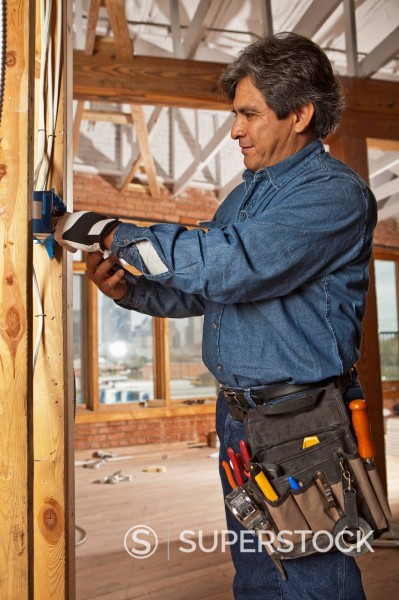 Stock Photo: 1589R-157679 Hispanic electrician working on construction site