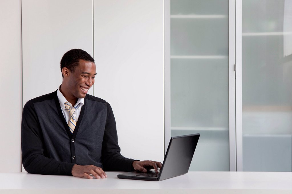 Black businessman typing on laptop : Stock Photo