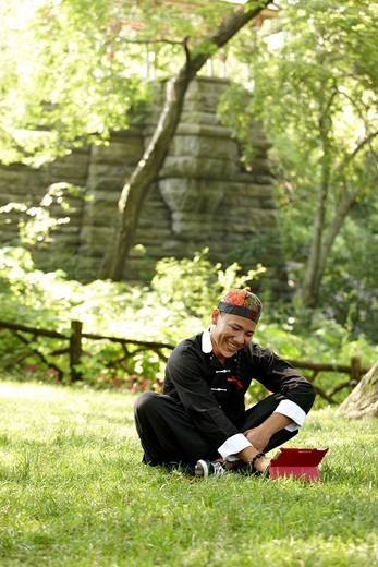 Man in traditional Asian clothing sitting in grass : Stock Photo