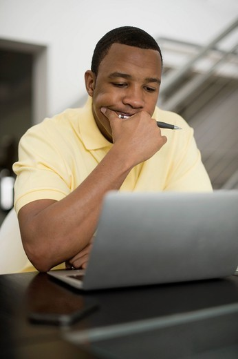 Mixed race businessman using laptop : Stock Photo
