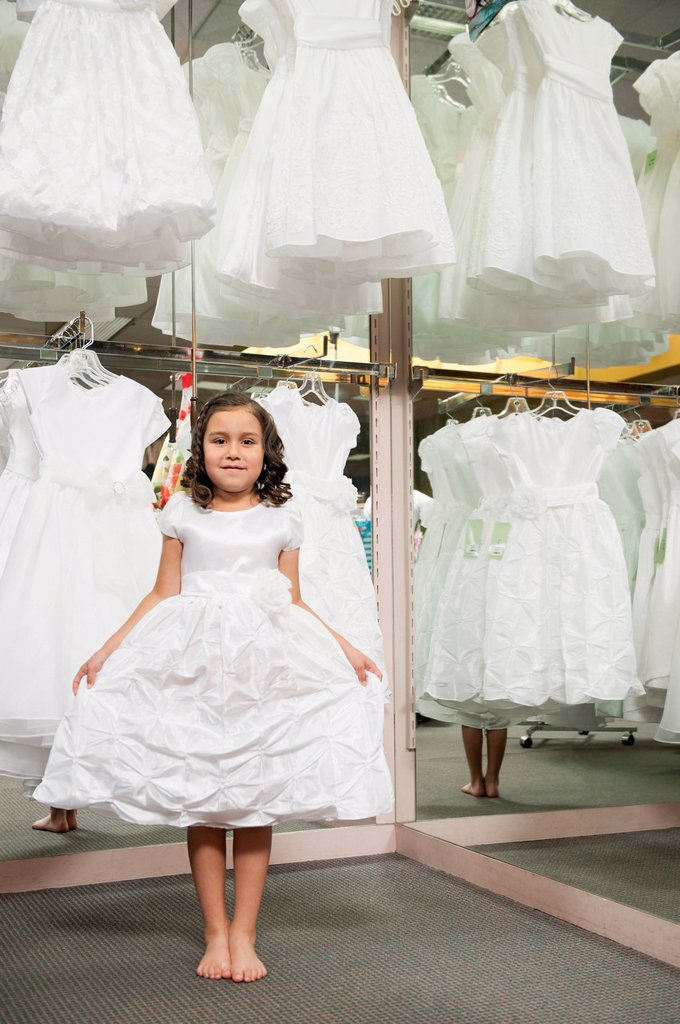 Mixed race girl trying on white dress : Stock Photo