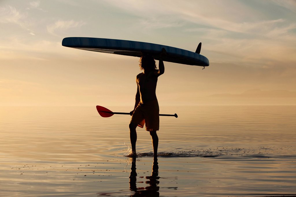 Stock Photo: 1589R-158236 Caucasian man walking in water carrying paddle board