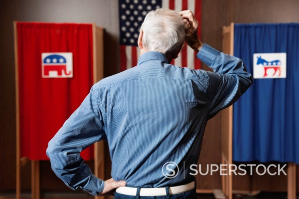 Caucasian voter waiting to vote in polling place : Stock Photo