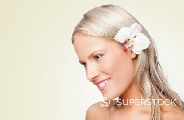 Stock Photo: 1589R-158339 Caucasian woman with flower behind her ear