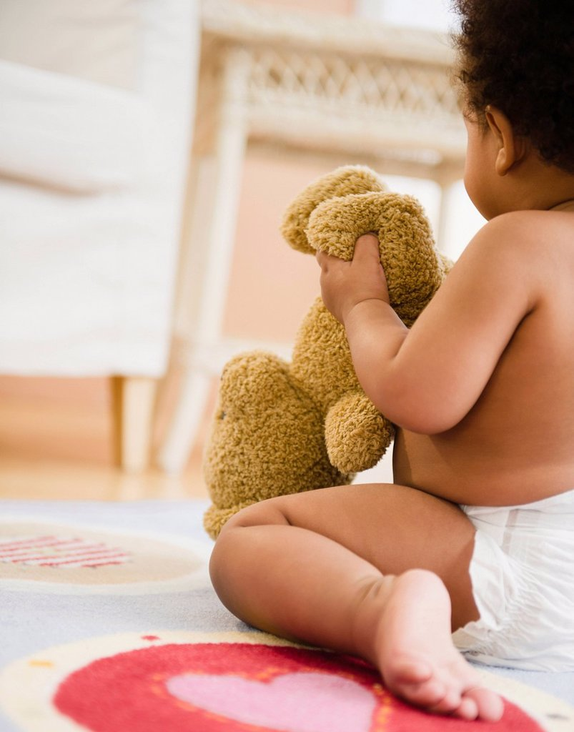 Stock Photo: 1589R-158507 Black baby girl holding teddy bear